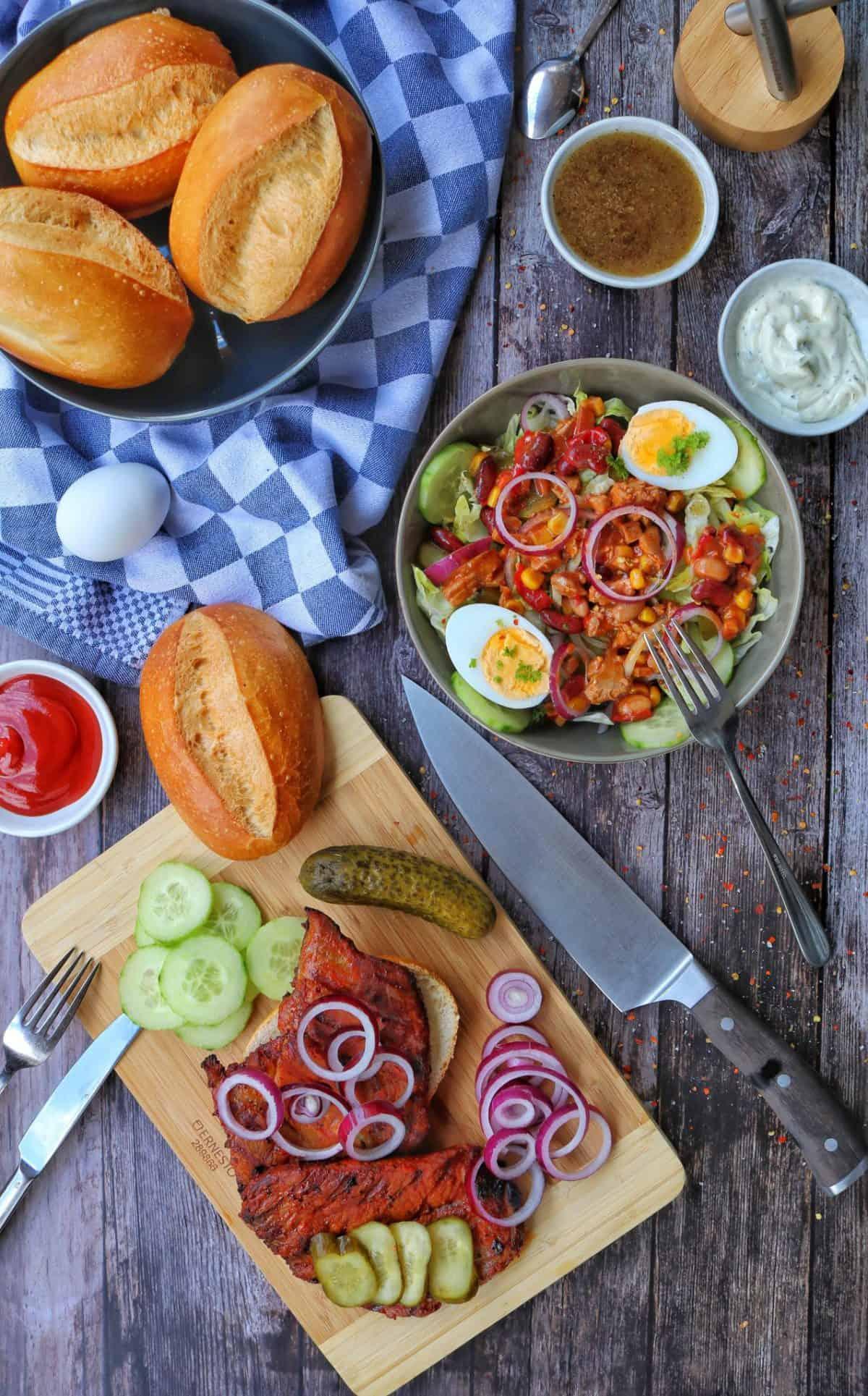 Steaks auf einem Brötchen. Dazu eine Salatbowl, weitere Brötchen und Deko