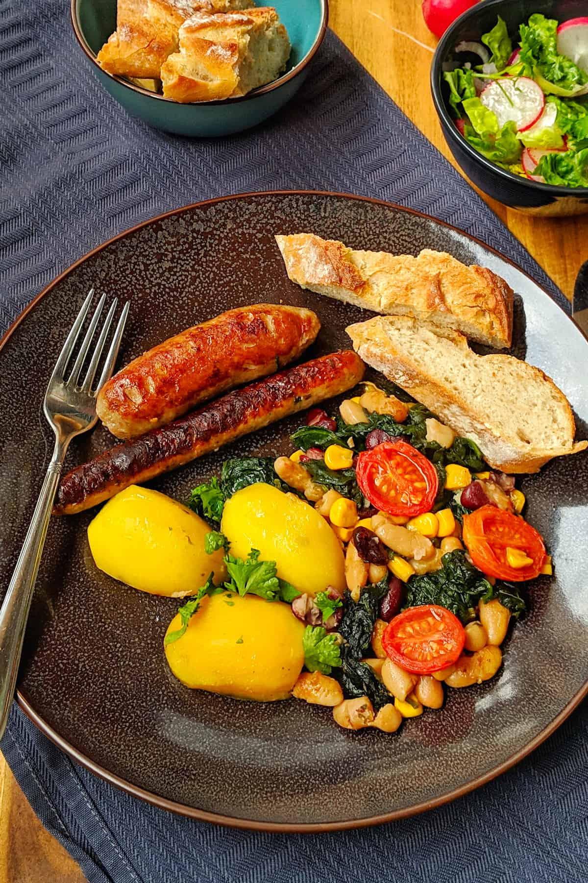 Ein dunkler Teller mit dem Cassoulet Gericht. Dahinter ein schälchen mit Brto und ein Schälchen mit Salat.