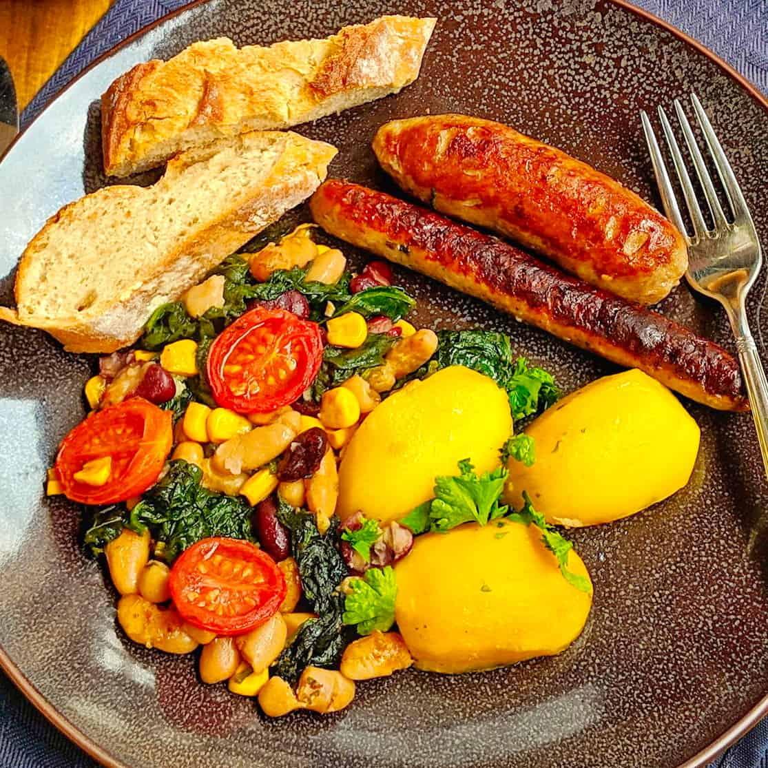 Ein dunkler Teller mit dem Cassoulet Gericht. Dahinter ein Schälchen mit Brot und ein Schälchen mit Salat.