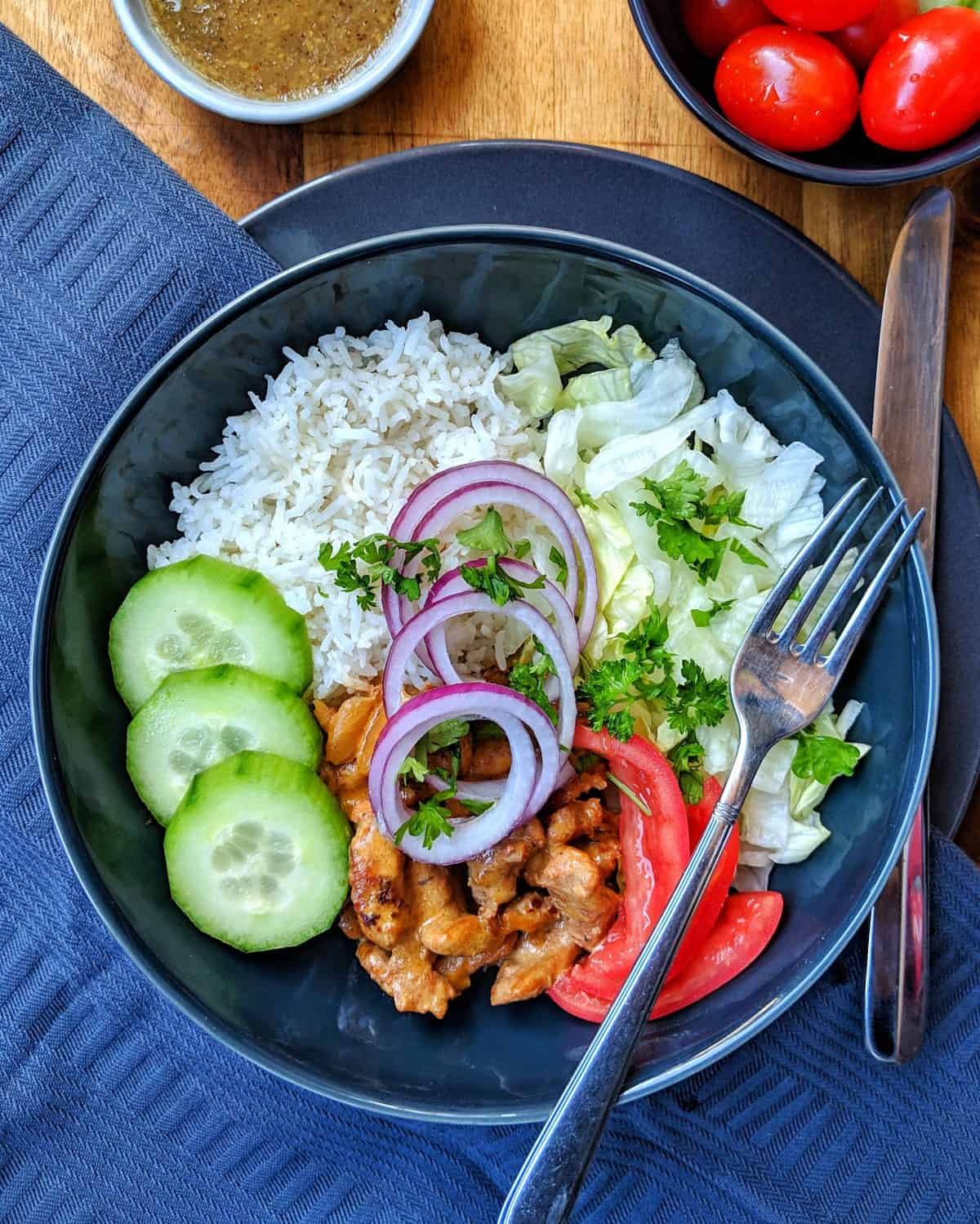 A dark plate with Gyros, rice and salad. In Addition, Decorating.