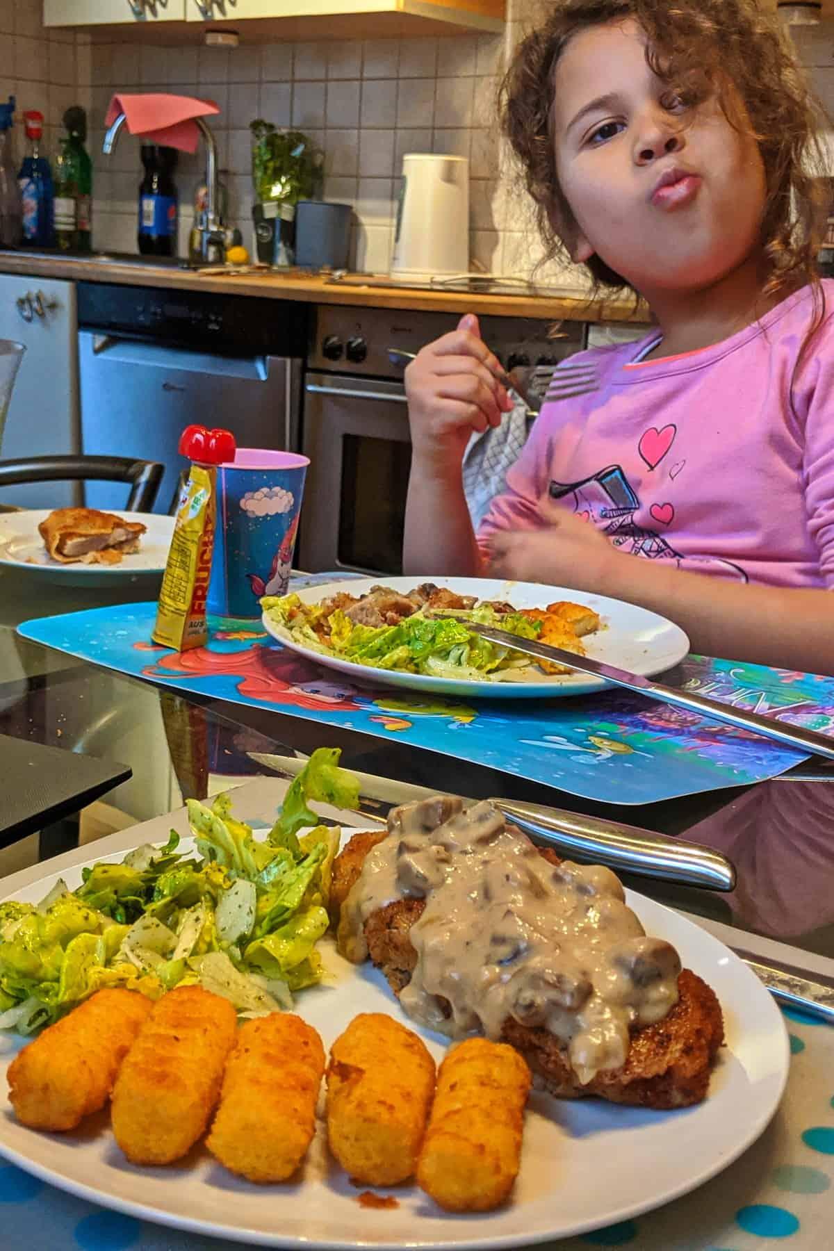 ein Kins am Esstisch, das Jägerschnitzel isst. Im Vordergrund einTeller mit Jägerschnitzel, Kroketten und Salat.