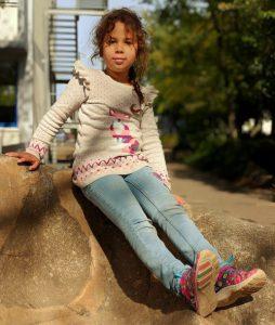Ein Kind das auf einem Stein sitzt