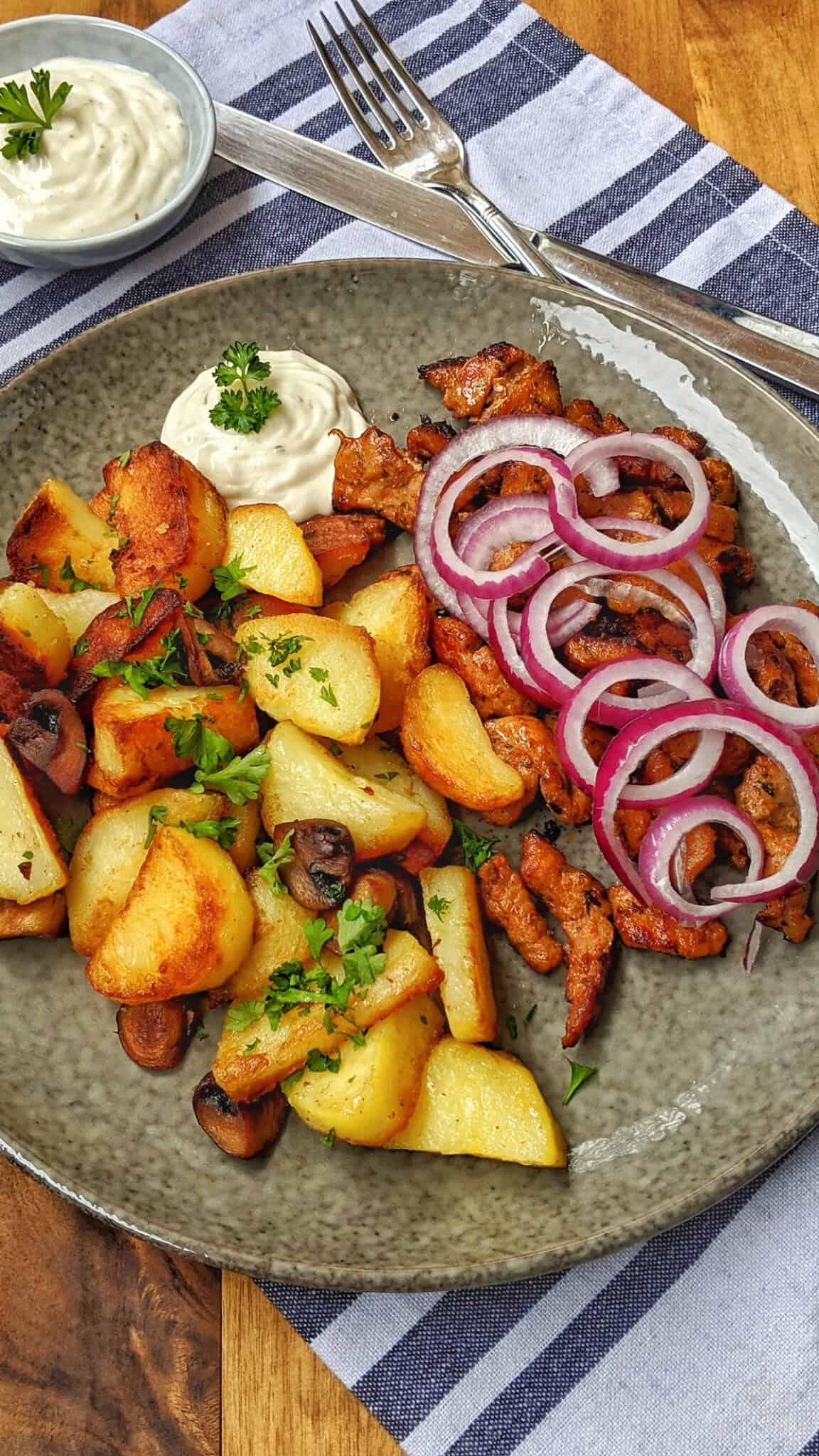Ein dunkler Teller mit Bratkartoffeln und Gyros.