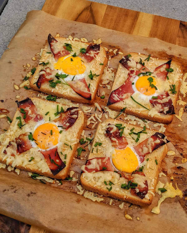 4 Überbackene Toastscheibeen mit Ei, Bacon, Käse und Schnittlauch