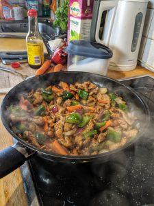 Zubereitung der Reispfanne mit Putengyros in einer Pfanne.
