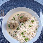 Königsberger Klopse mit Reis angerichtet auf einem Teller