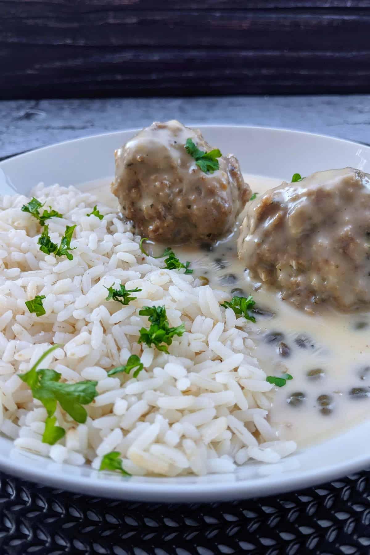 Einen Teller mit Königsberger Klopsen und Reis