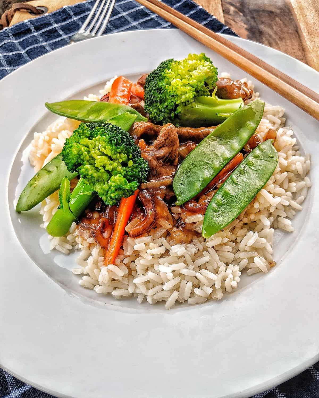 Ein Teller mit Rindfleisch Streifen mit Brokkoli und Zuckerschoten auf Basmati Reis.