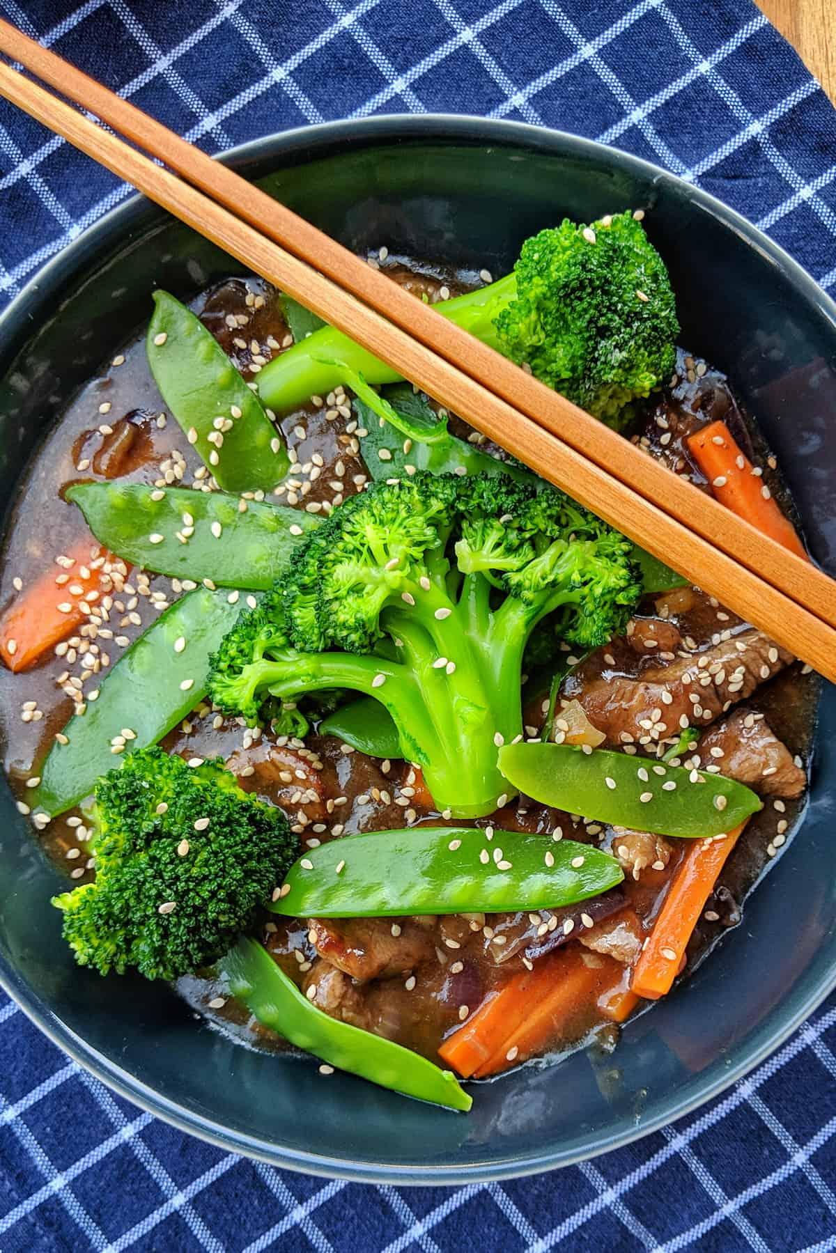Ein dunkler tiefer Teller mit Rindfleisch Streifen mit Brokkoli und Zuckerschoten. Dahinter eine Schale mit Reis.