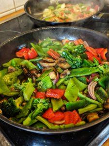 Eine Pfanne in dem das asiatische Rindfleisch Gericht zubereitet wird.