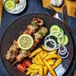 Ein dunkler Teller mit Souvlaki Spießen, Pommes und einer Salatgarnitur