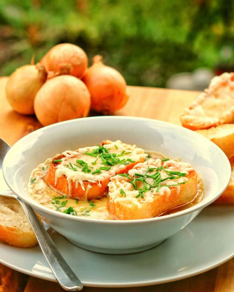 Einen Teller mit Zwiebelsuppe und Baguette