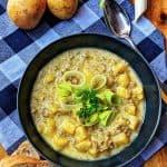 Ein dunkler tiefer Teller mit einer Käse-Lauch-Suppe