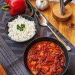 Eine Schüssel Chili con Carne und eine Schüssel mit Reis. Im Hintergrund Deko.