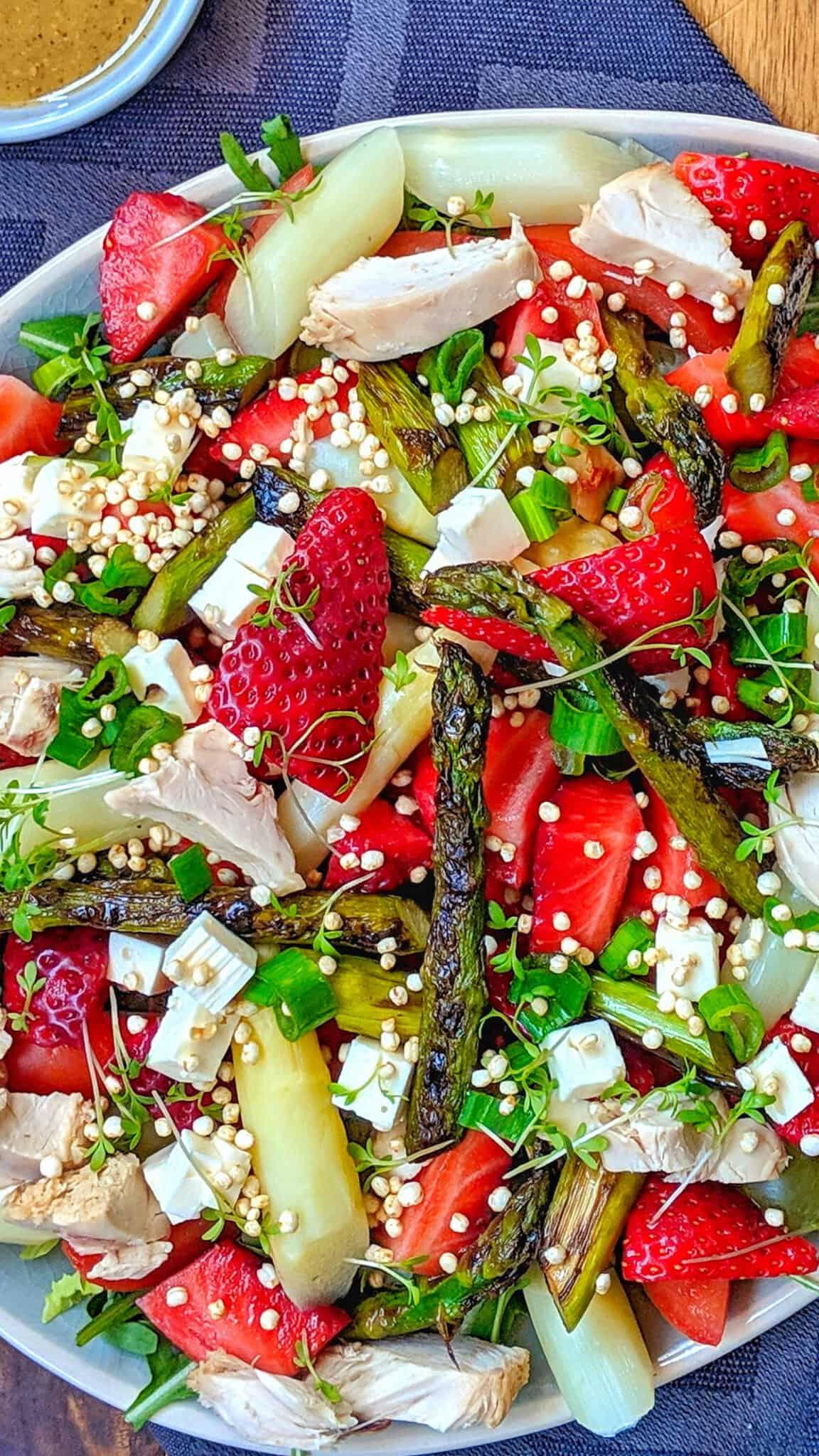 Ein Teller mit Erdbeer-Spargel Salat mit Deko im Hintergrund