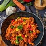 Ein tiefer Teller mit Jollof Reis und Gemüse