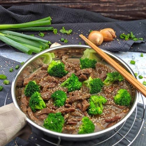 Eine Pfanne mit Beef and Broccoli. Im Hintergrund Deko.
