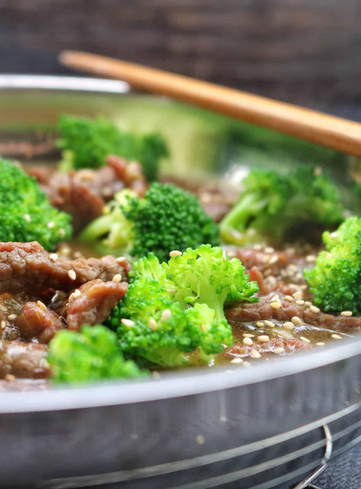 Eine Pfanne mit Beef und Brokkoli in Nahaufnahme mit Essstäbchen.