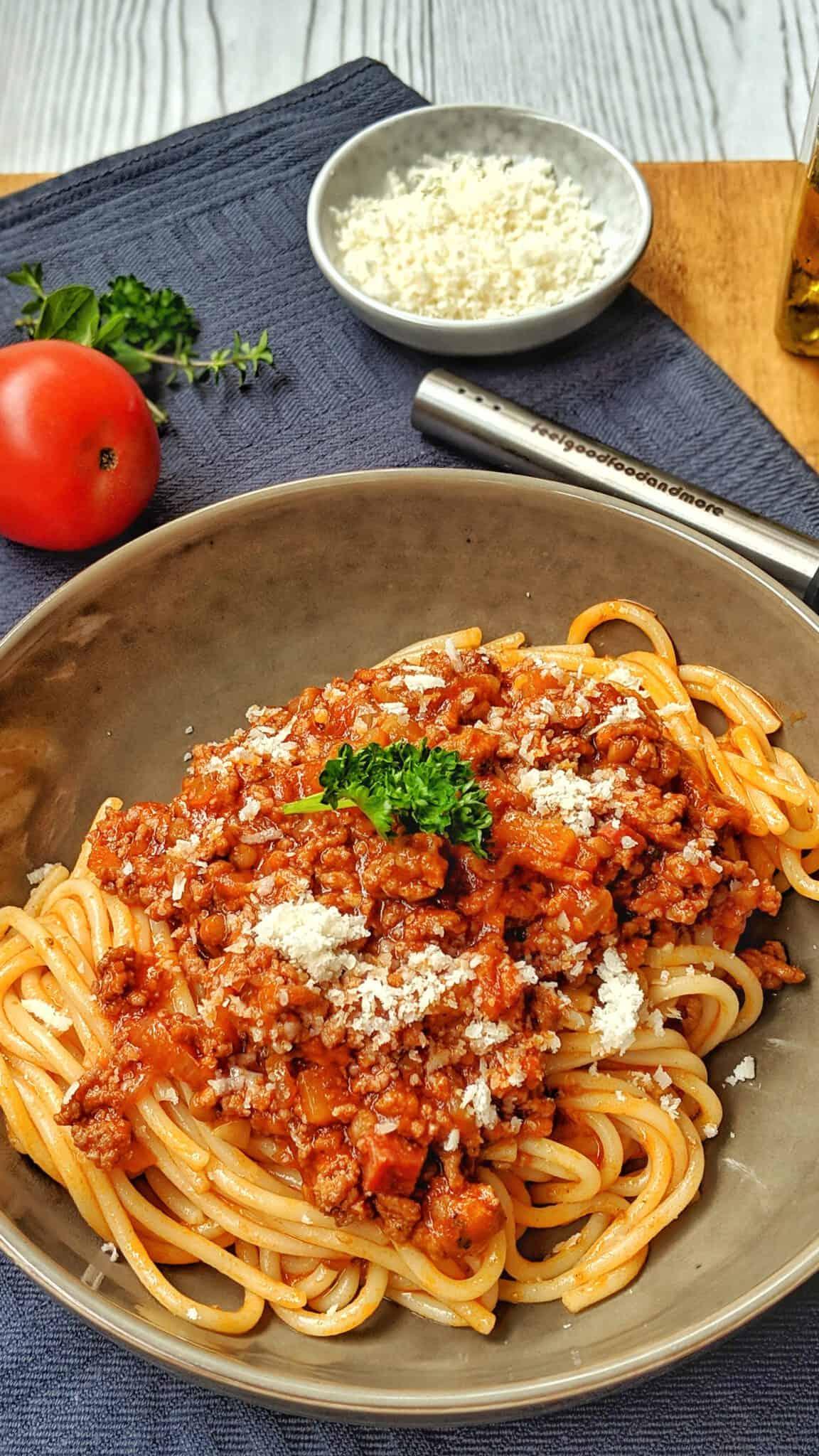 Ein tiefer Teller mit Bolognese mit Chorizo und Linsen. Aussen herum Deko.