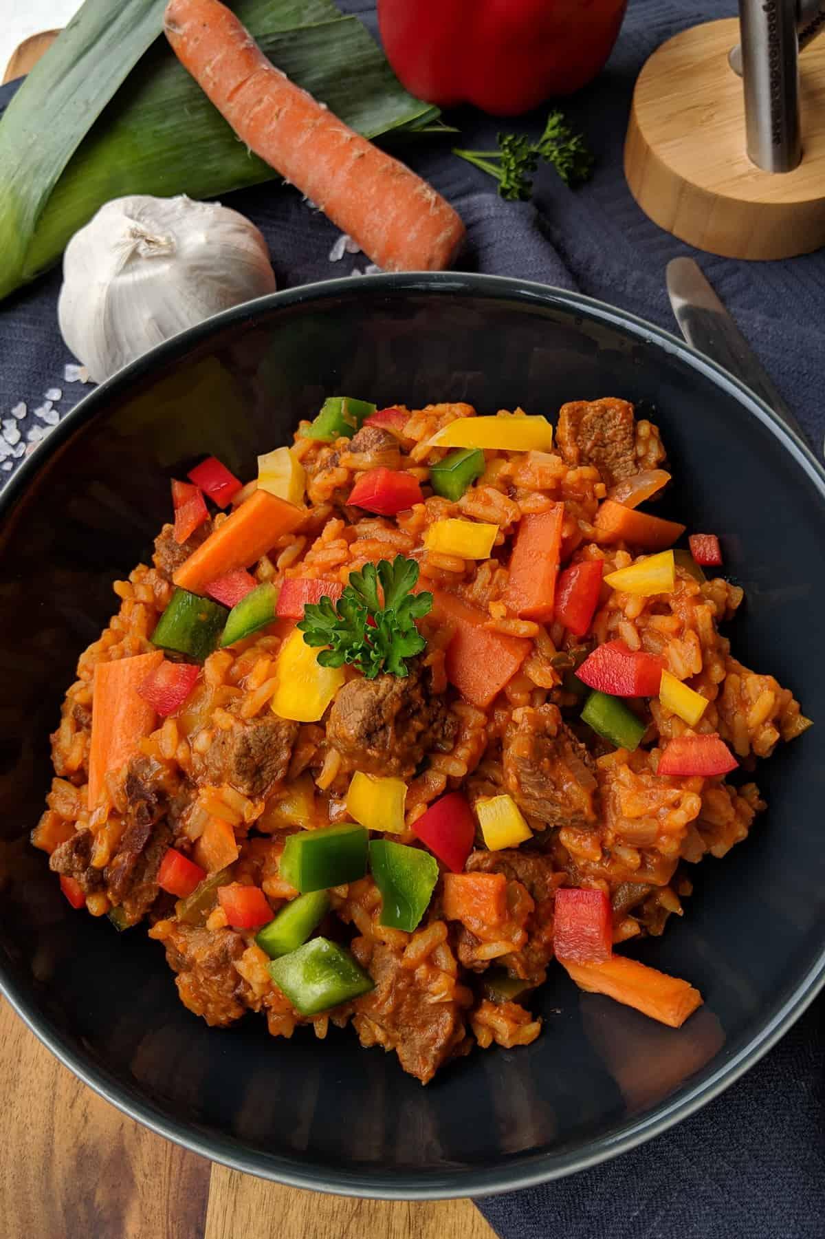 Ein tiefer Teller mit Jollof Reis und Gemüse.