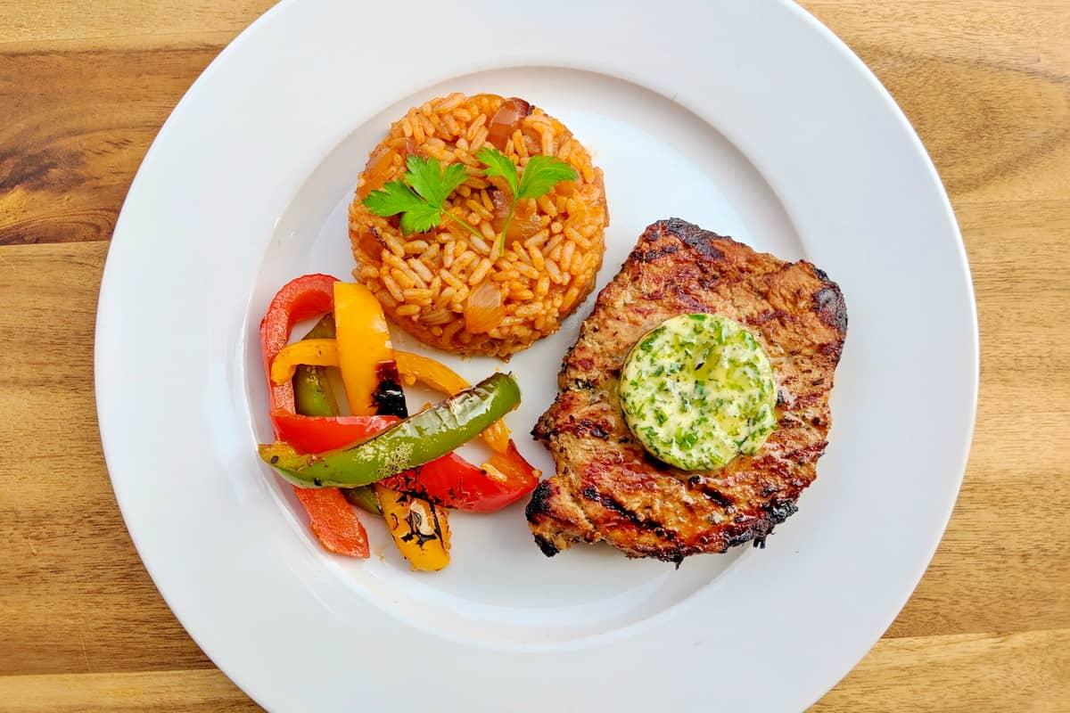 Ein weisser Teller mit Jollof Reis, Gemüse und einem Steak mit selbstgemachter Kräuterbutter..