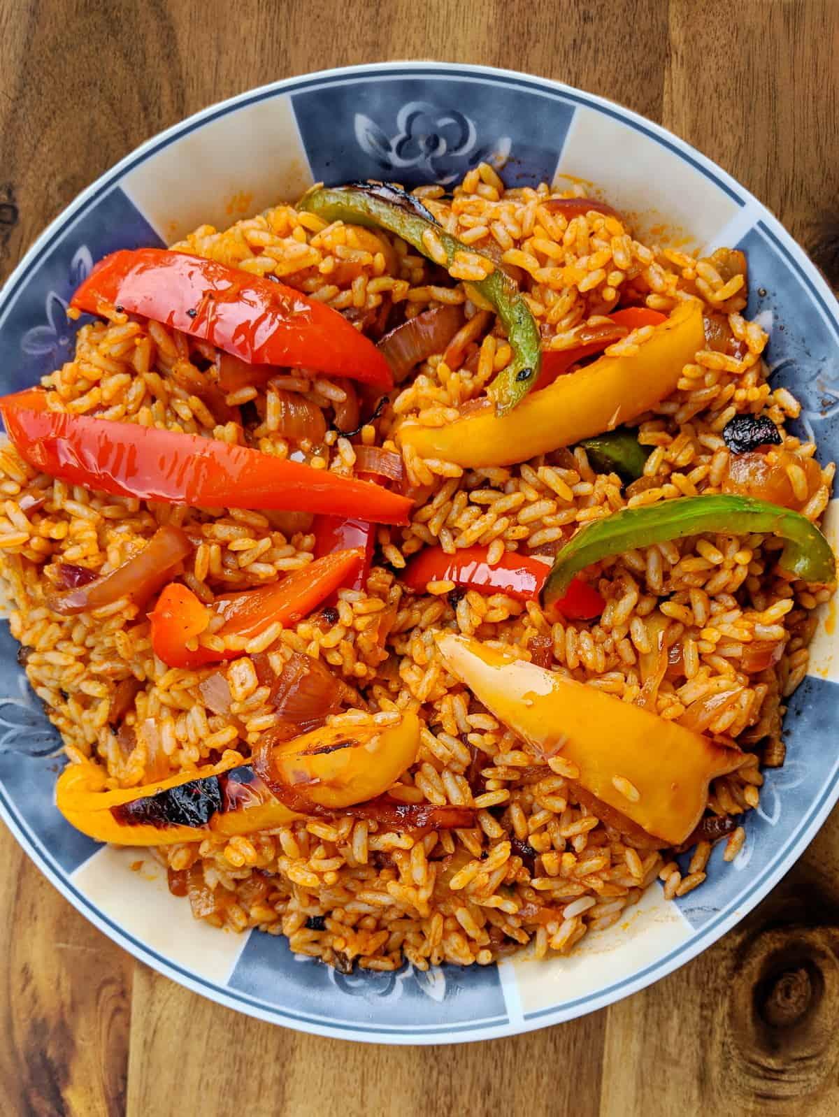 Eine bunte Schüssel mit Jollof Reis und gegrilltem Gemüse.