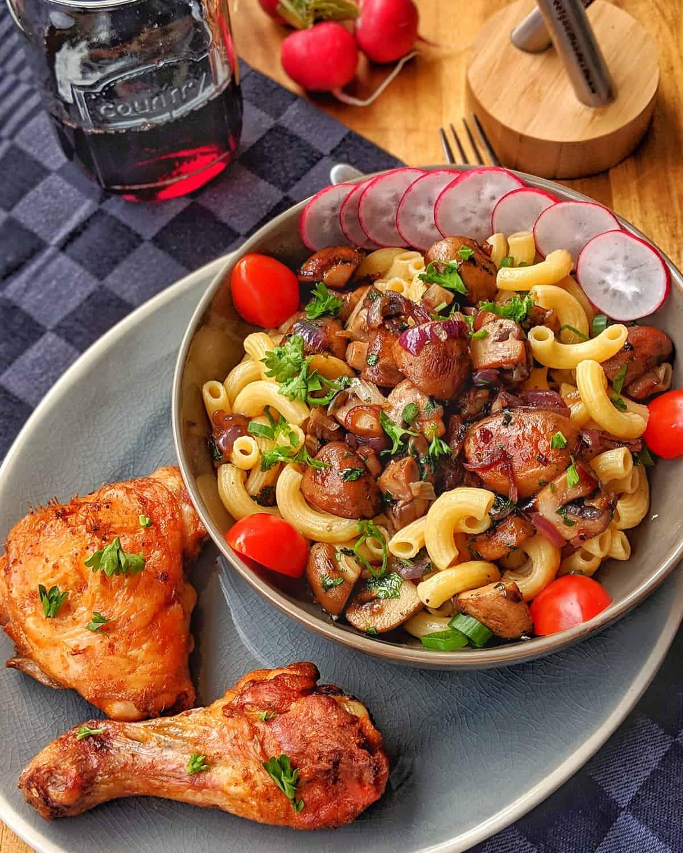 Eine Schale mit Pasta und Pilzen. Daneben 2 Hähnchenteile. Im Hintergrund Deko.