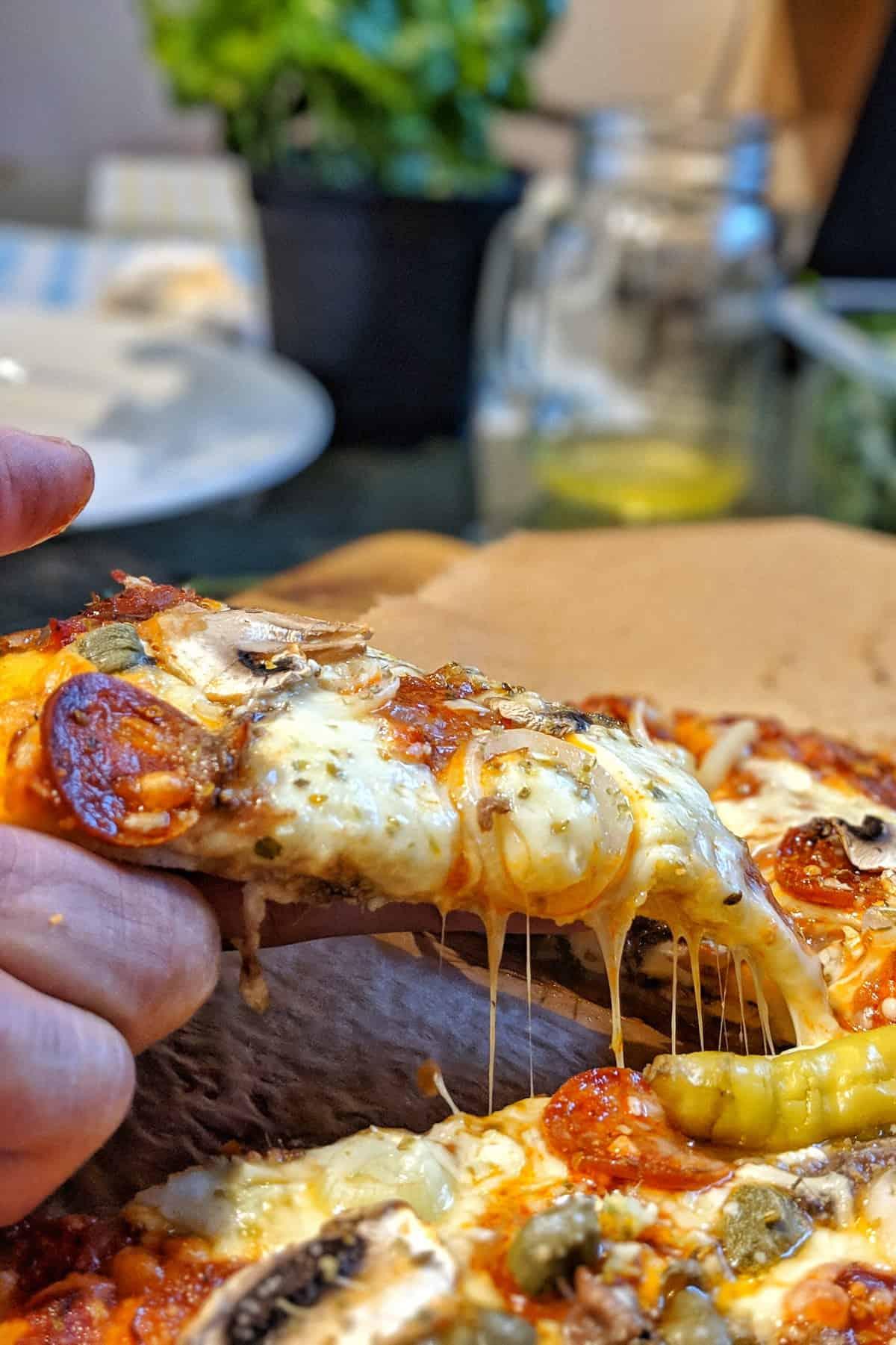 Eine Hand die ein Stück Pizza hoch zieht.