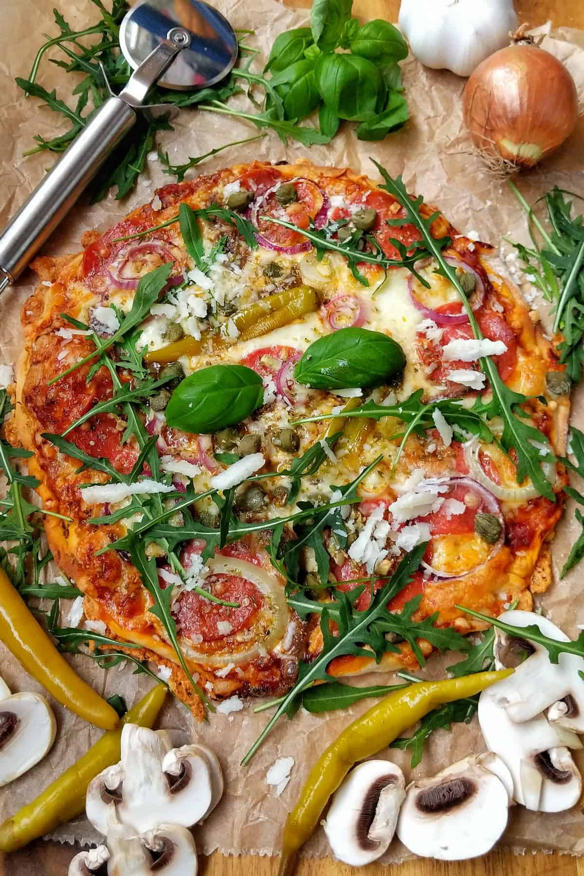 Eine Pizza auf einem Backpapier. Aussenrum Gemüse als Deko.