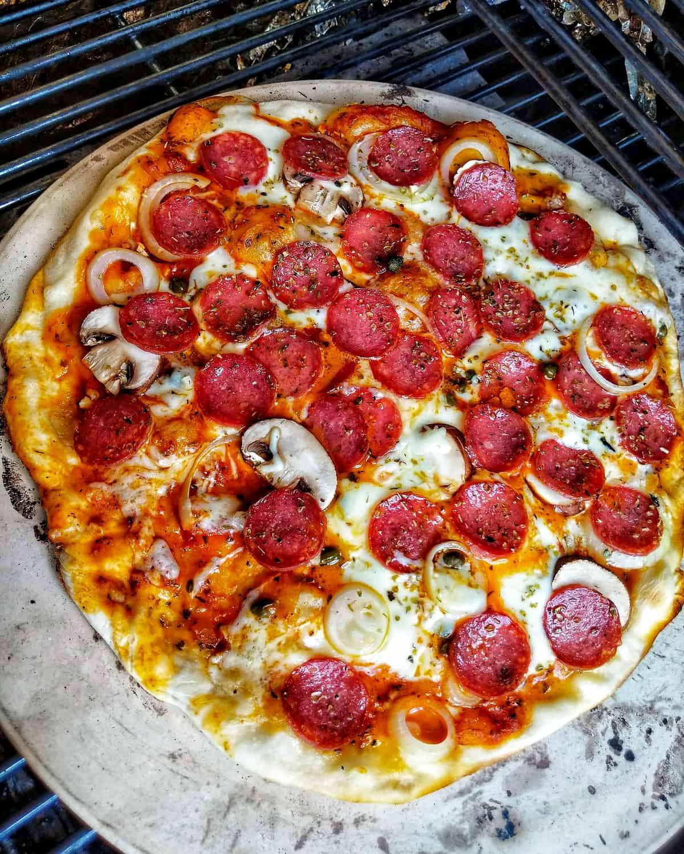 Eine Salami Pizza auf einem Pizzastein auf einem Grill.