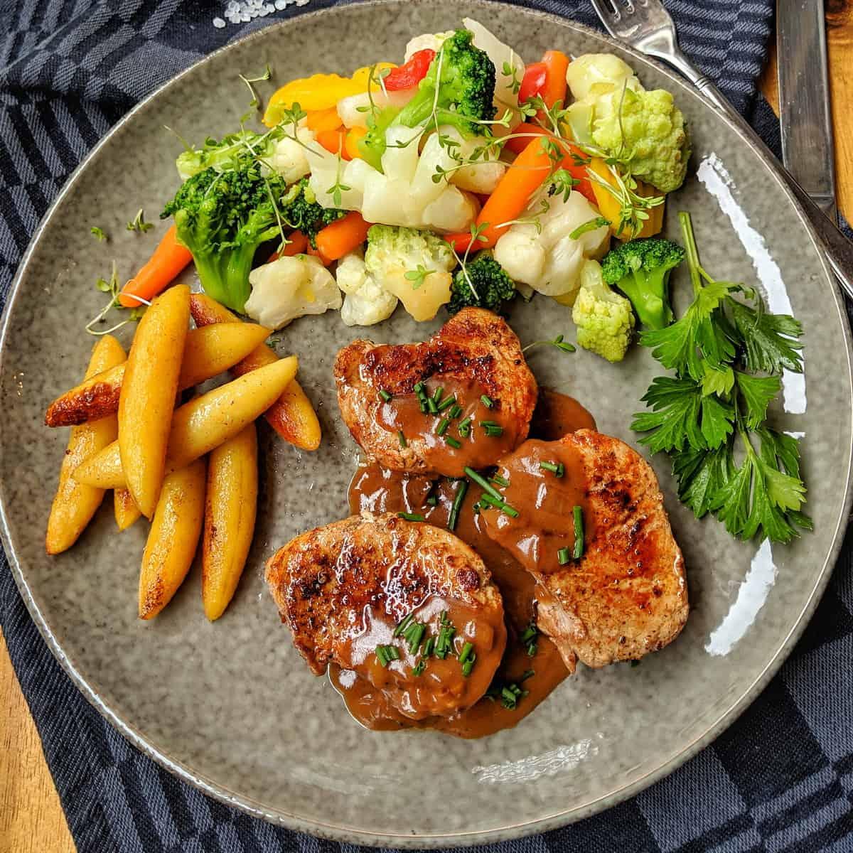 Ein dunkler Teller mit Schweinelende in Pfefferrahm mit Schupfnudeln und buntem Gemüse. Dahinter Deko.