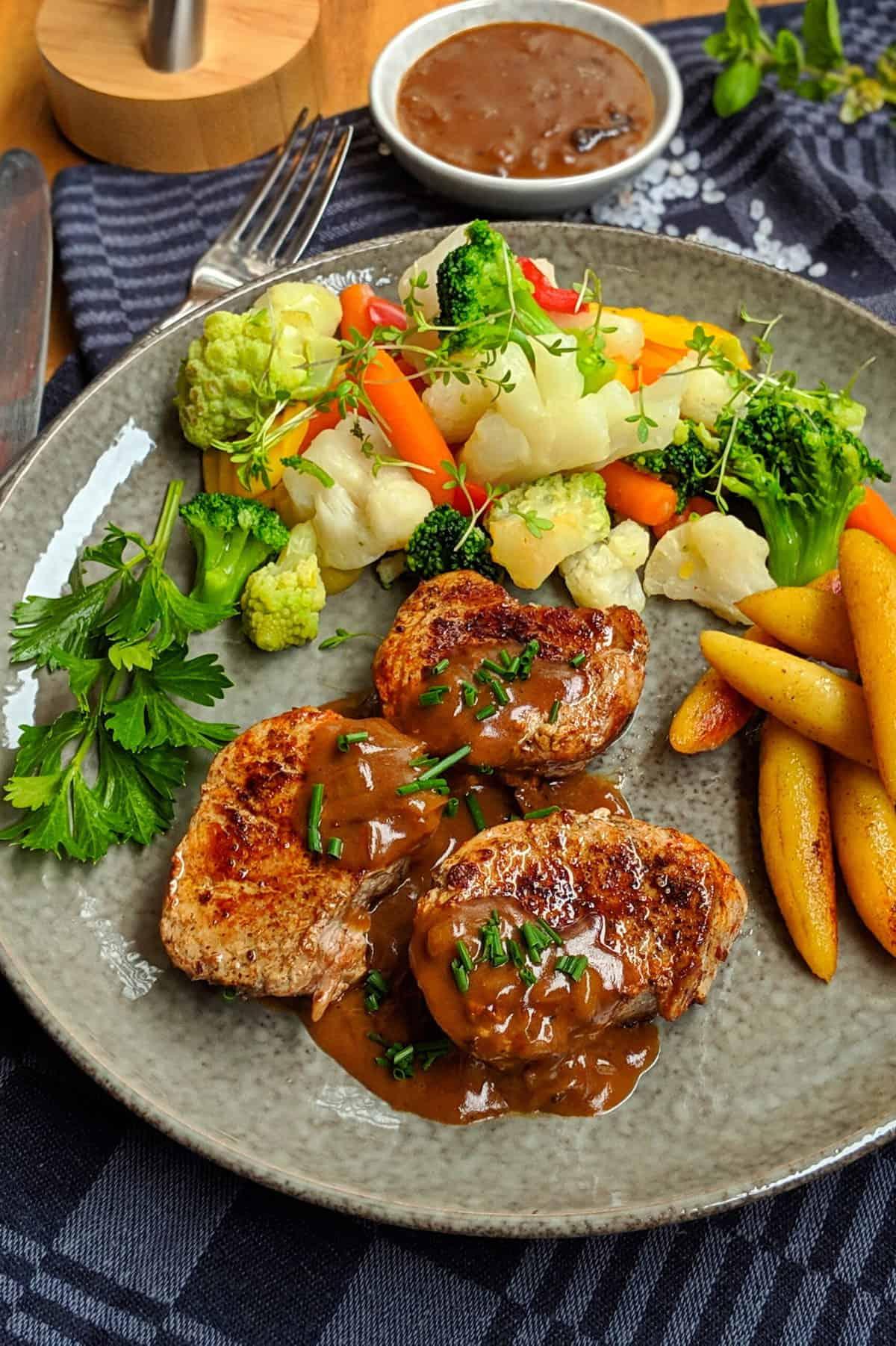 Ein dunkler Teller mit Schweinelende in Pfefferrahm mit Schupfnudeln und buntem Gemüse.
