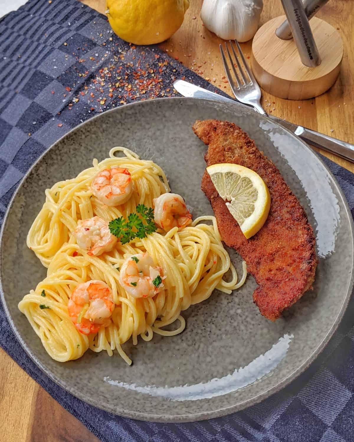 Ein grauer Teller mit Spaghetti Aglio Olio mit Scampi und Parmesanschnitzel. Dahinter eine Zitrone, Knoblauch und Deko.