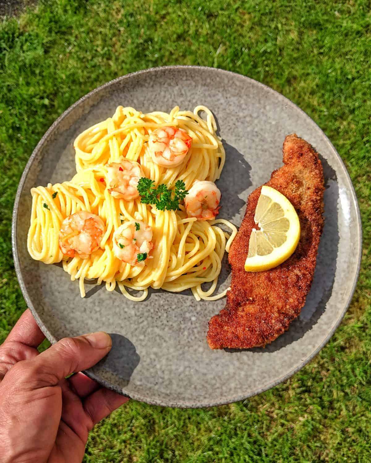 Eine Hand hält einen grauenTeller mit Spaghetti Aglio Olio mit Scampi und Parmesanschnitzel.