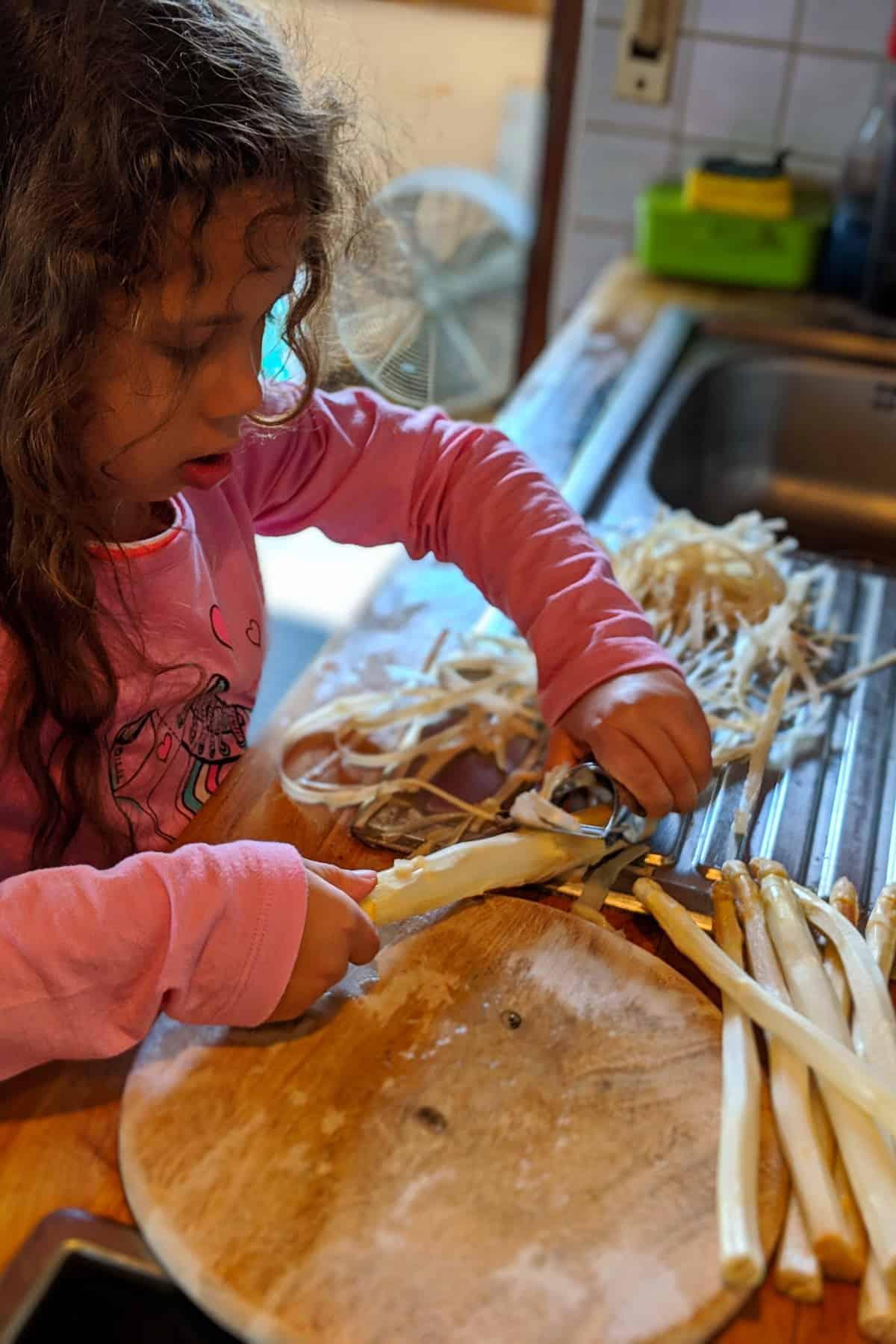 Ein Kind schält Spargel in der Küche.
