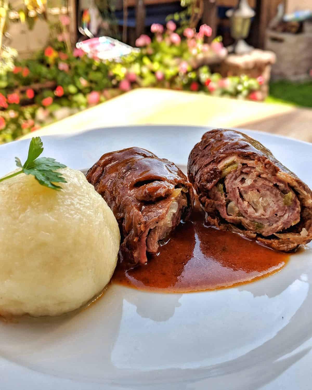 Ein weisser Teller mit Rinderrouladen und Kartoffelknödel