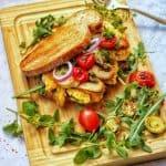 Ein dekaratives Rührei Sandwich mit vielen Veggies auf einem Holzbrett