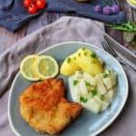 Ein blauer ovaler Teller mit einem panierten Kotelett, Kartoffeln und Kohlrabi. Im Hintergrund Deko