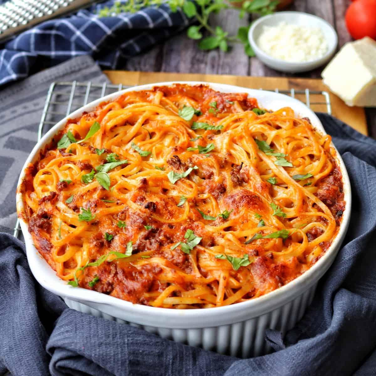Eine weiße Auflaufform mit überbackenen Spaghetti, im Hintergrund Deko