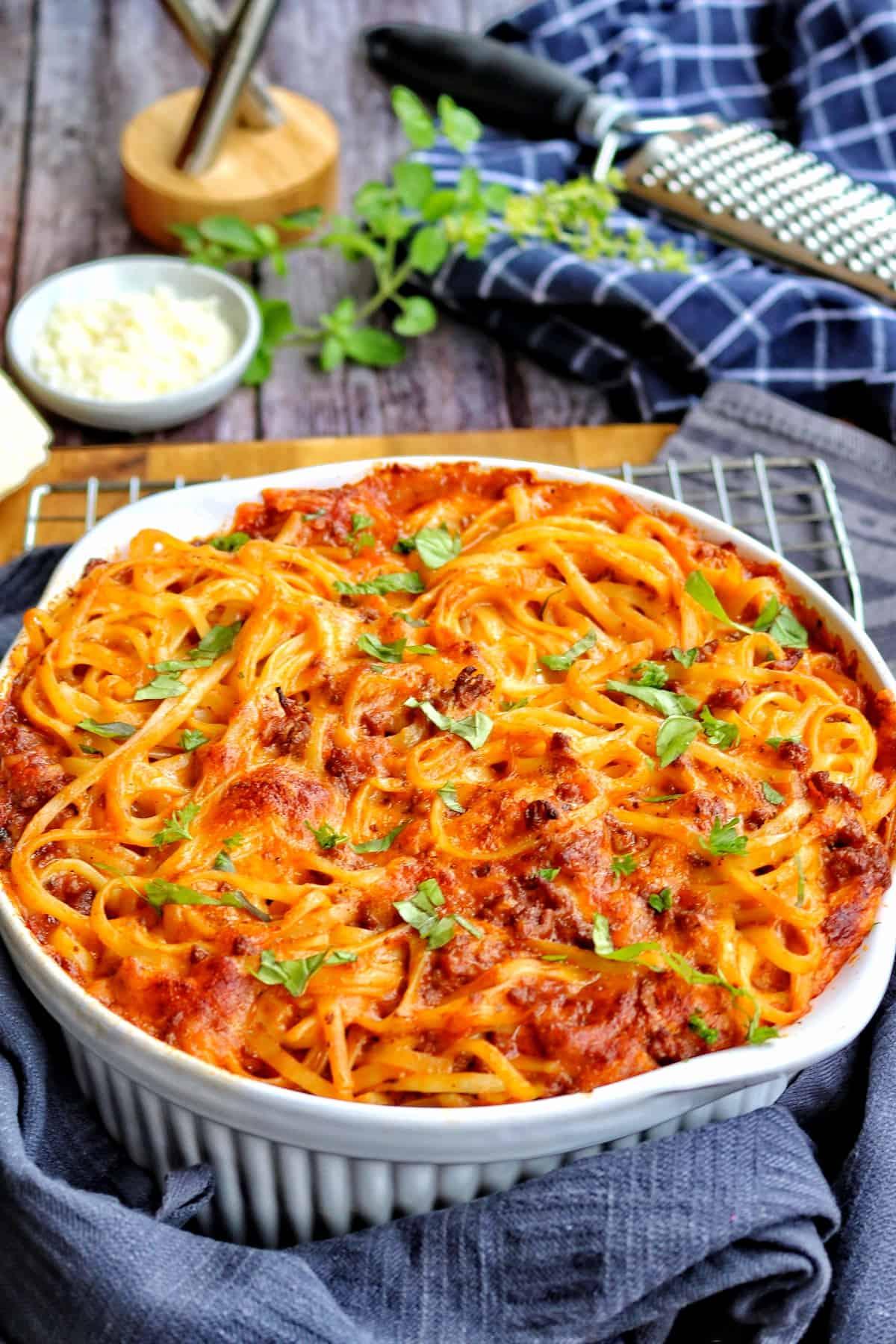 Eine weiße Auflaufform mit überbackenen Spaghetti, im Hintergrund Deko.