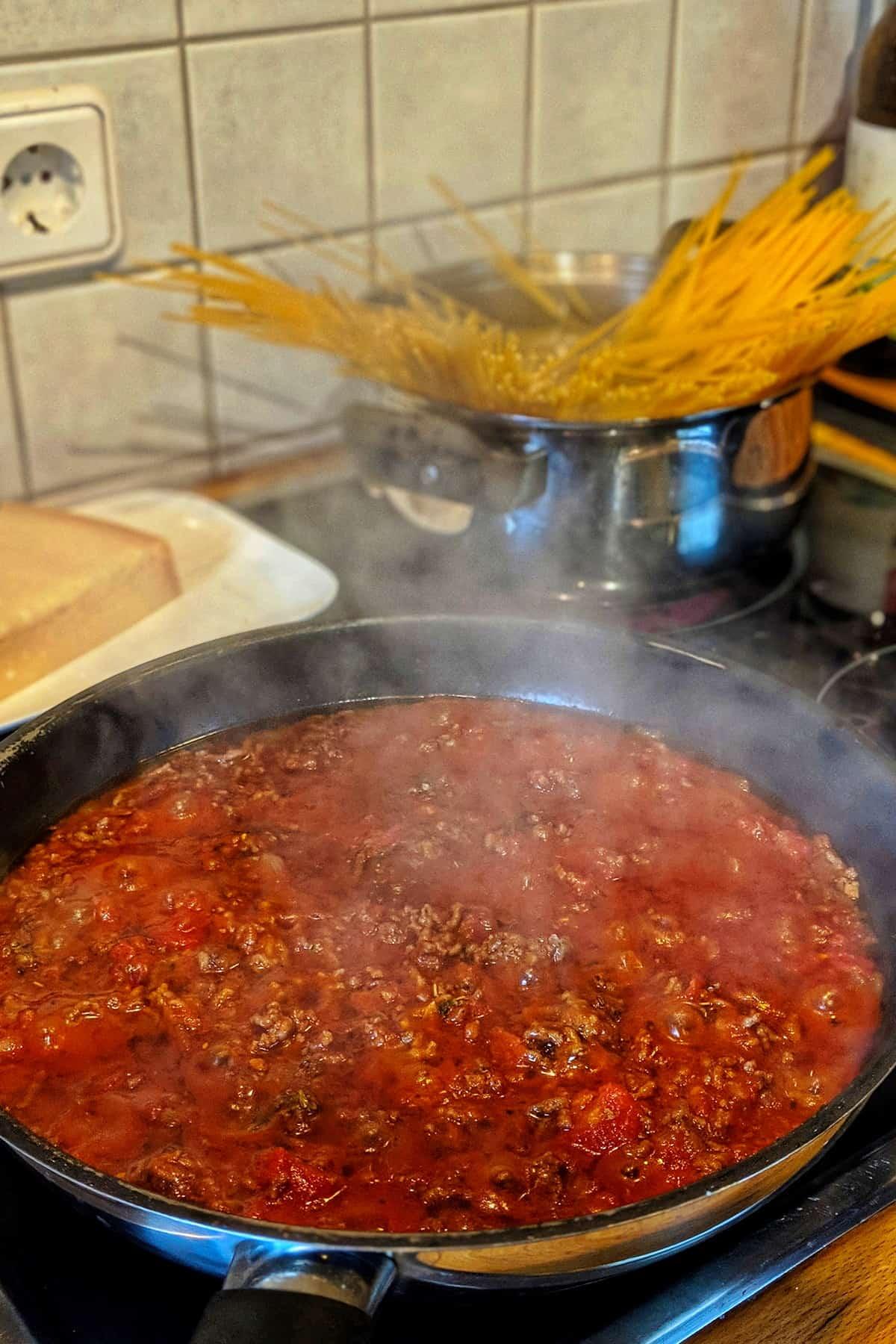 Eine Pfanne mit Blitz-Bolognese Sosse. Im Hintergrund ein Topf mit Spaghetti.