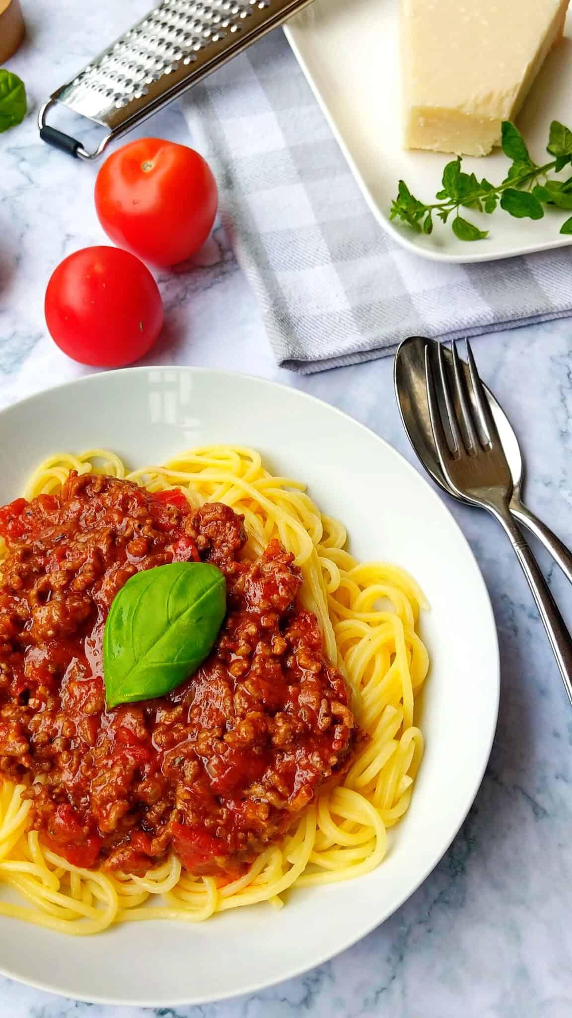 Ein Teller mit Spaghetti und Bolognese Soße. Im Hintergrund Parmesan und Deko