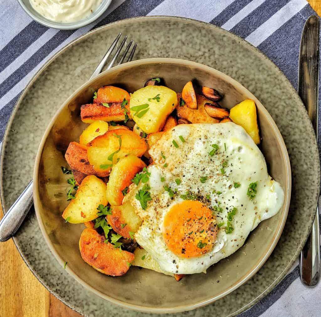 Ein tiefer Teller mit Bratkartoffeln und Spiegelei