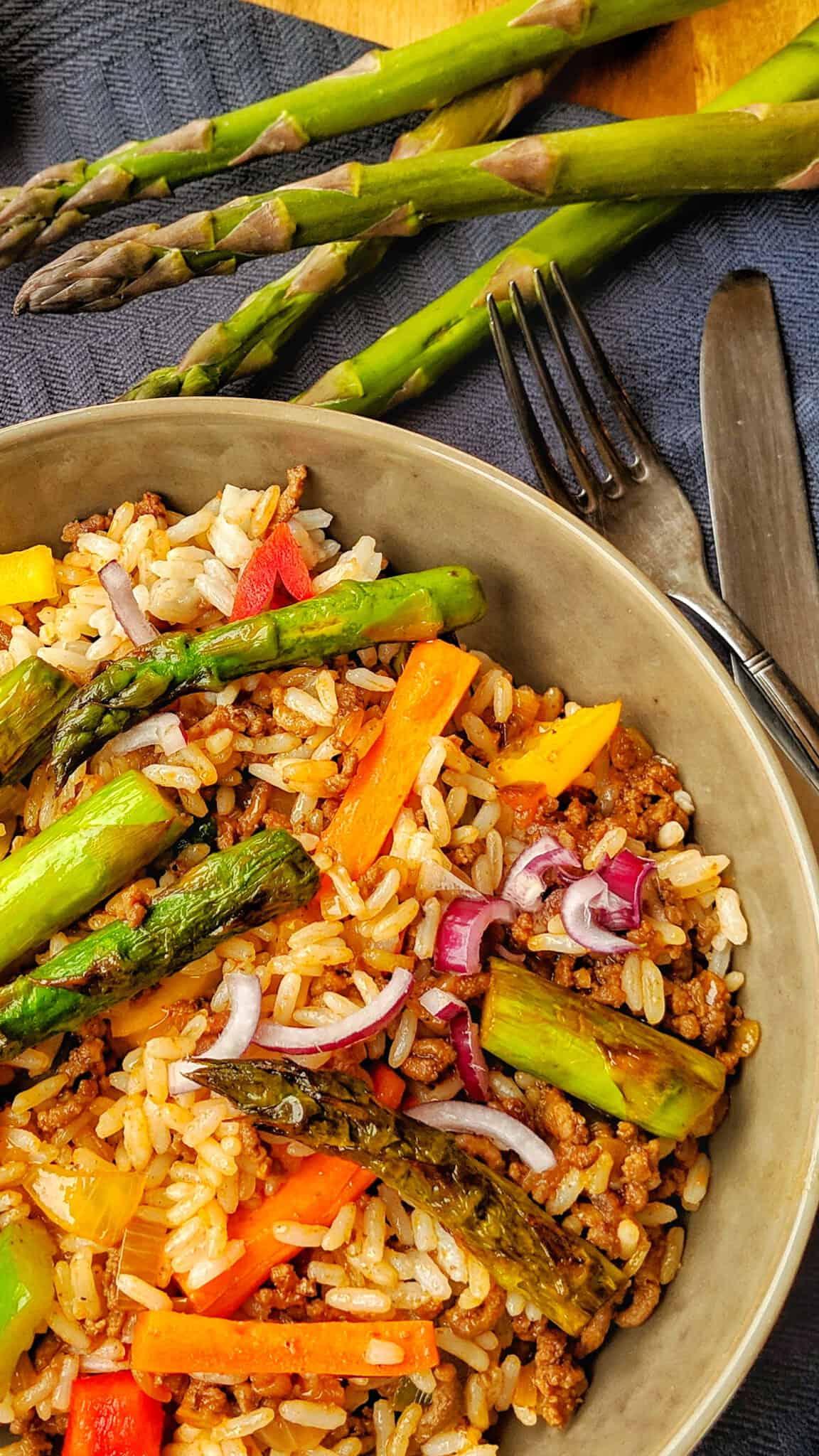 Ein dunkler tiefer Teller mit der Schnellen Hackfleisch-Reis-Pfanne. Dahinter grüner Spargel als Deko.