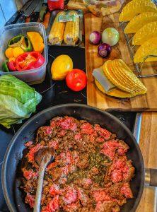 Zubereitung von Tacos. Das Hackfleisch wird in einer Pfanne angebraten