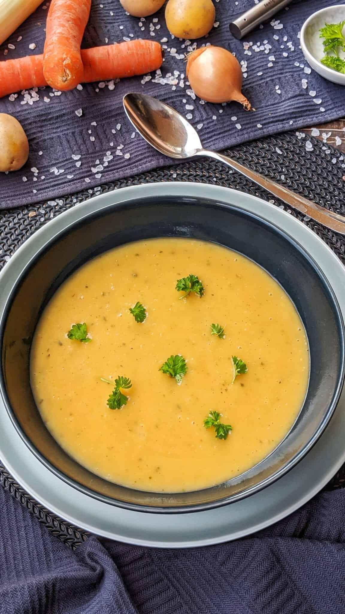 Ein Teller mit Kartoffelsuppe. Darüber Gemüse als Deko.