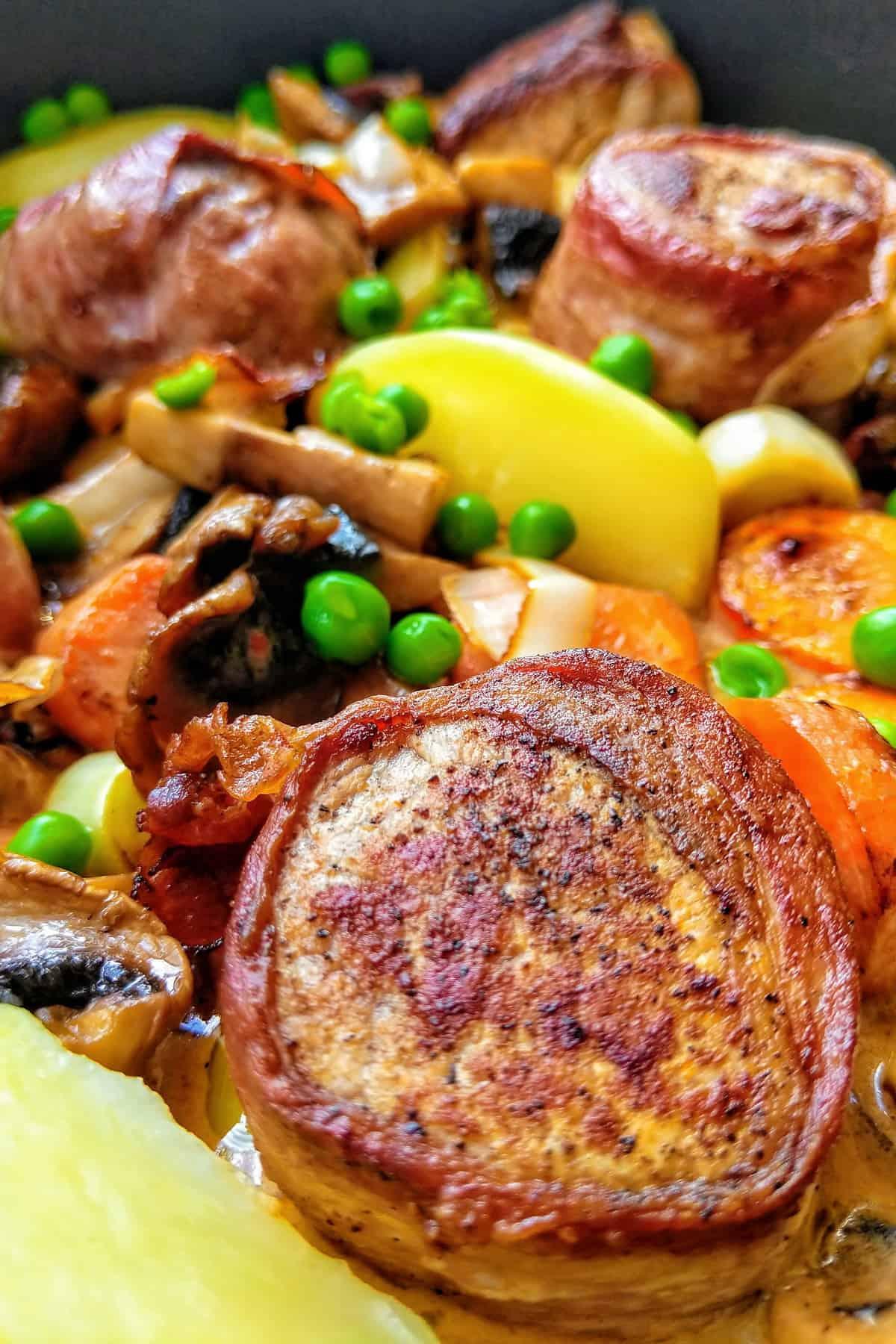 Eine Nahaufnahme von Medaillons mit Bacon und buntem Gemüse in Senfsoße.