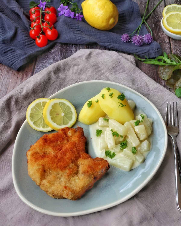 Ein ovaler Teller mit einem panierten Kotelett, Kohlrabigemüse und Kartoffeln. Im Hintergrund Deko.
