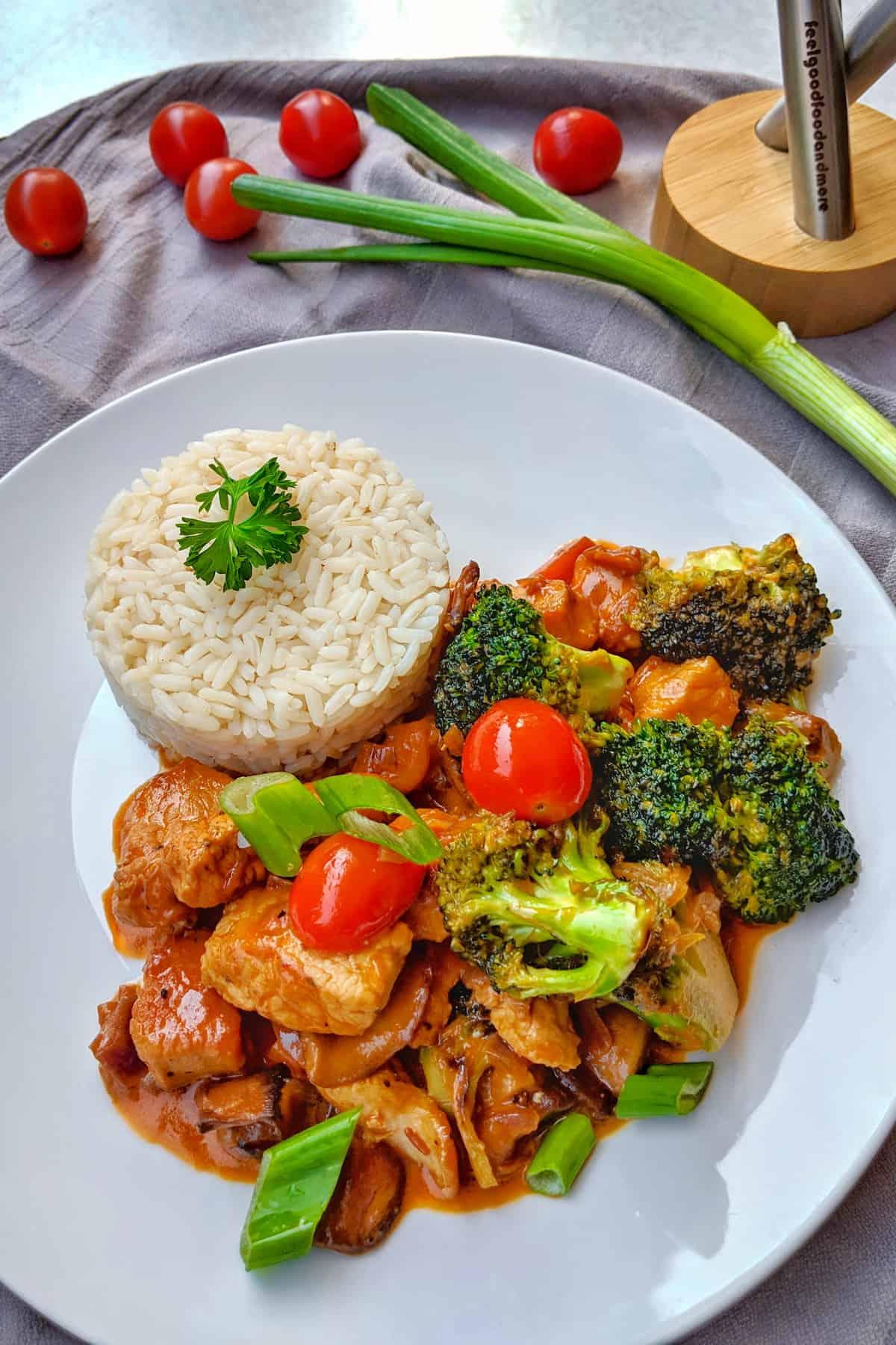 Ein Teller mit Putengeschnetzeltes mit Champignons und Brokkoli. Dazu Reis.