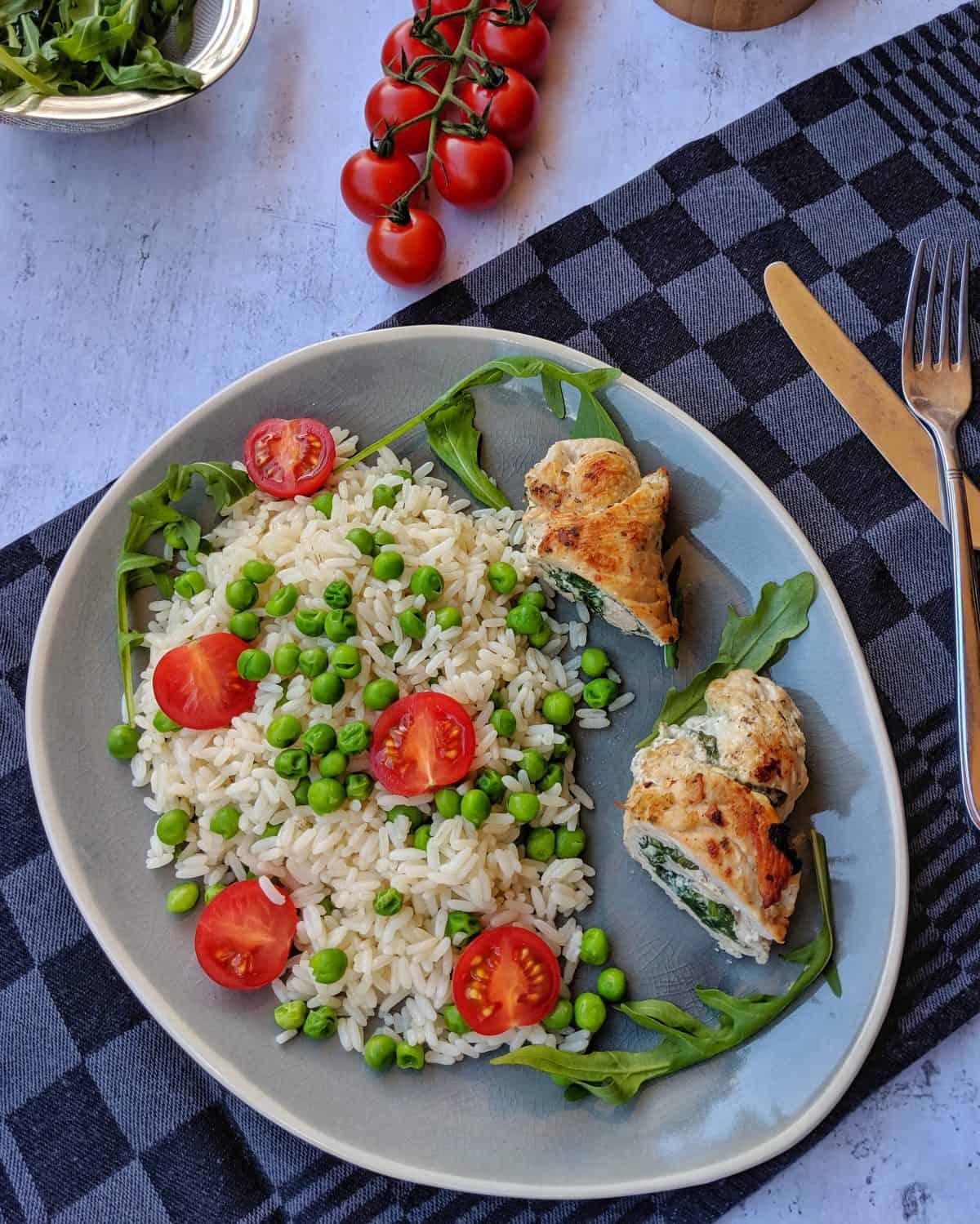 Ein ovaler Teller mit Putenrouladen mit Spinat-Ricotta Füllung auf gebuttertem Erbsen-Tomatenreis. Dahinter Deko.